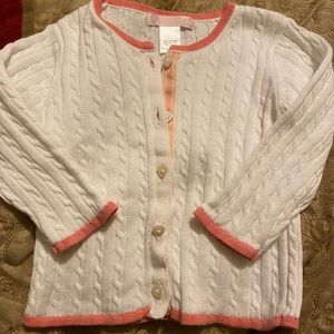 White button down sweater with pink trim.